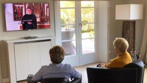 zwei Personen schauen Gottesdienst im Fernsehen