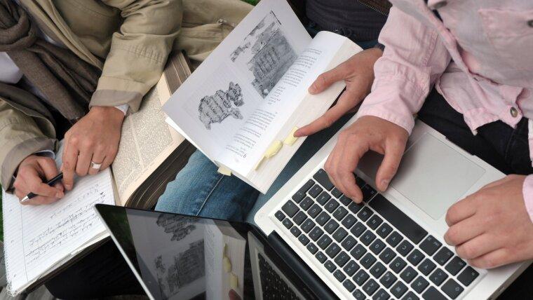 Studierende mit Laptop und Büchern.
