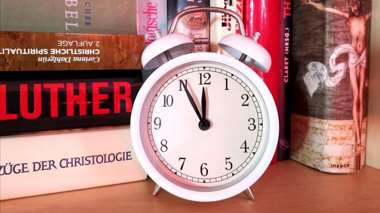 Uhr vor theologischer Fachliteratur